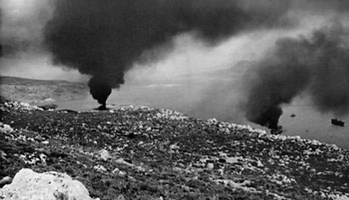 The harbor at Suda Bay, Crete, where two ships, hit by German bombers, burn themselves out, May 1941 (Imperial War Museum: E 3039E)