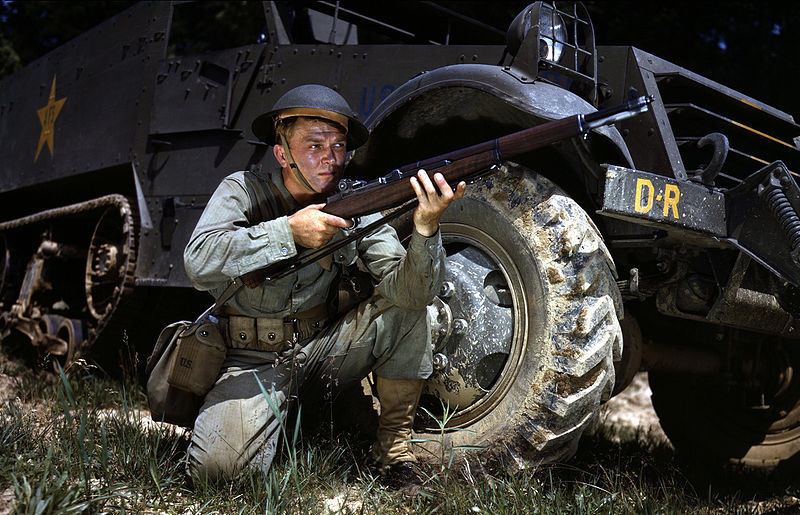 Infantryman in herringbone twill fatigues, kneeling in front of M3 half-track, holds and sights an M1 Garand rifle, Fort Knox, KY, June 1942 (Library of Congress: fsac 1a35212)