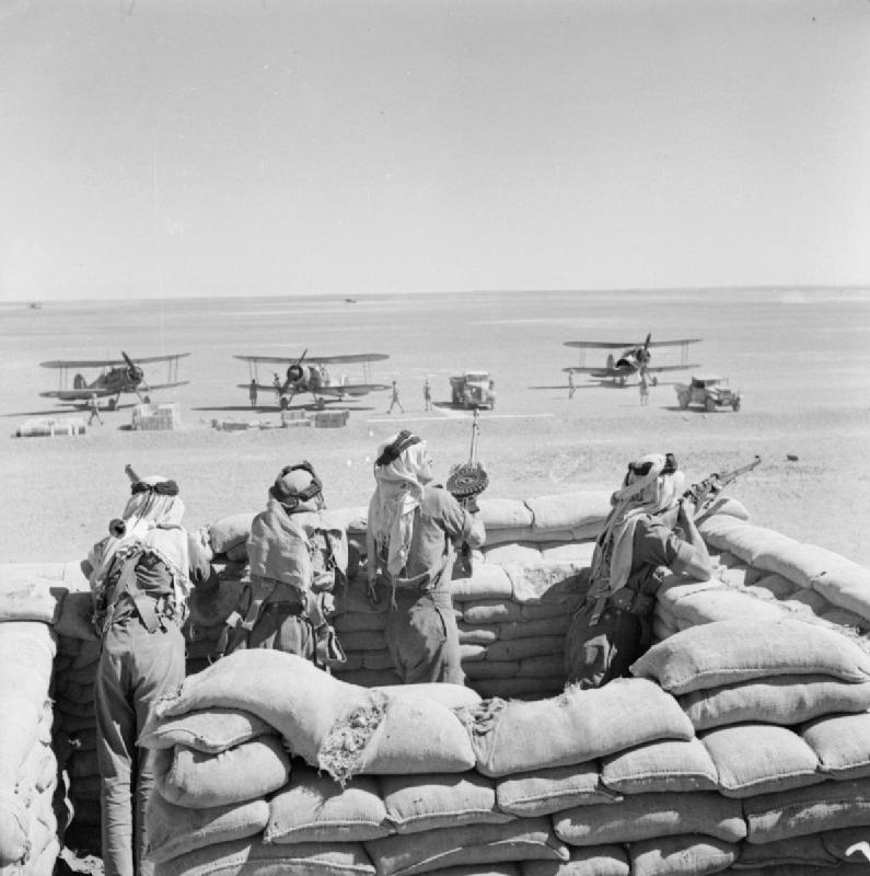 Arab Legionnaires guard the landing ground in Transjordan, as RAF Gloster Gladiators refuel on journey from Ismailia, Egypt, to besieged Habbaniya, Iraq, 8 May 1941 (Imperial War Museum: CM 774)