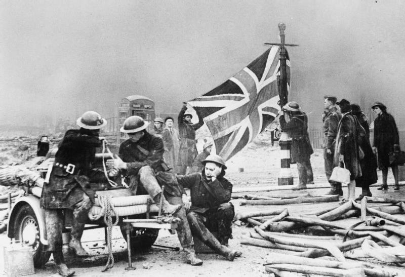 Firemen hang a Union Jack on a lamppost after an air raid on Plymouth, England, early 1941 (Imperial War Museum: HU 36253)