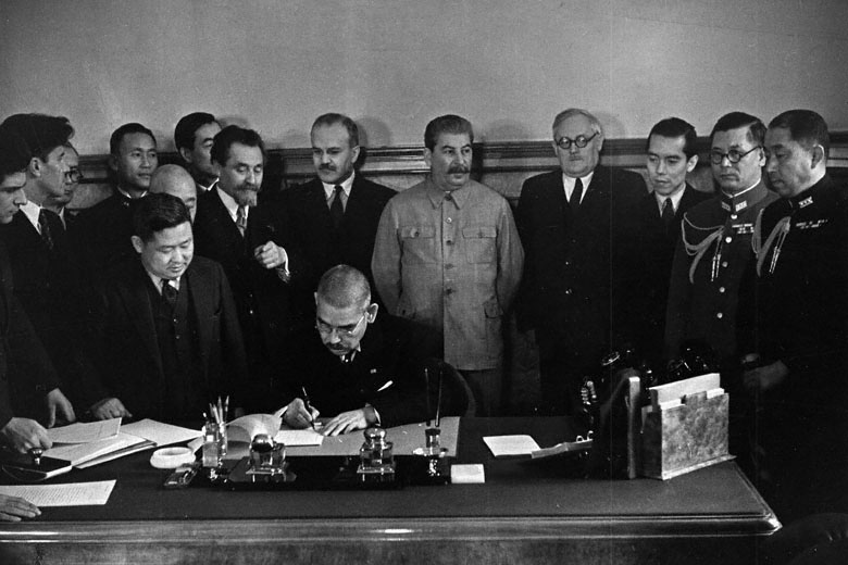Japanese Foreign Minister Matsuoka signing the Soviet-Japanese Neutrality Pact, 13 Apr 1941, Molotov and Stalin in background (public domain via Russian Archives and Wikipedia)