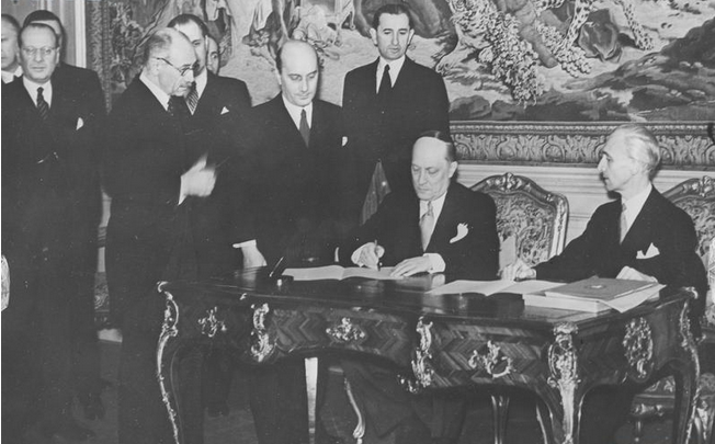 Foreign Ministers Aleksandar Cincar-Marković of Yugoslavia and László Bárdossy of Hungary signing the Treaty of Eternal Friendship between Yugoslavia and Hungary; Hungarian Prime Minister Pál Teleki (with glasses) is on the left, Budapest, 14 March 1941 (public domain via Wikipedia)