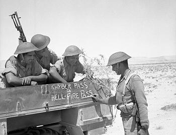 """Troops of Indian 4th Division decorating their truck with """"Khyber Pass to Hellfire Pass,"""" noting their service in South Asia and North Africa, 21 Jun 1941 (Imperial War Museum: 4700-32 E 3660)"""