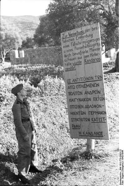 """Sign erected by the Germans at Kandanos, Crete, which reads: """"Kandanos was destroyed in retaliation for the bestial ambush murder of a paratrooper platoon and a half-platoon of military engineers by armed men and women."""" (German Federal Archive: Bild 101I-779-0003-22)"""