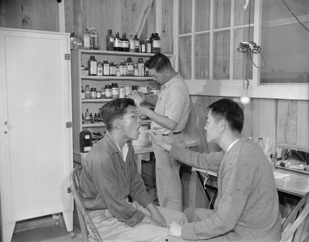 Japanese-Americans Dr. K. H. Taria and pharmacist Tom Arase at work, Jerome War Relocation Center, Arkansas, 17 Nov 1942 (US National Archives)