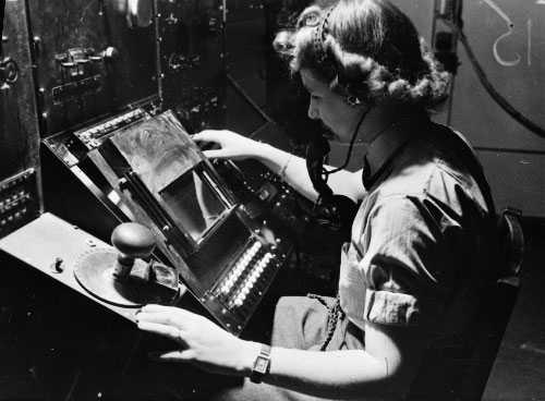 WAAF radar operator Denise Miley plotting aircraft on the CRT (cathode ray tube) of an RF7 Receiver in the Receiver Room at Bawdsey Chain Home Station (Imperial War Museum: CH 15332)