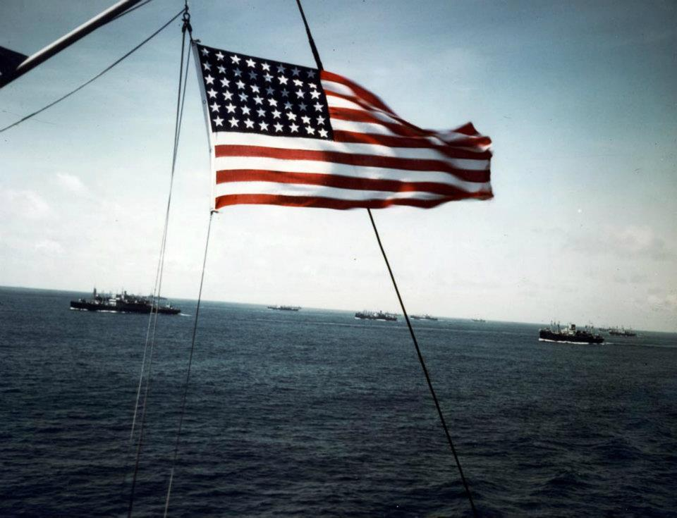 Convoy at Sea, World War II. The US flag frames a convoy of transports and cargo ships (US Army photograph, USA C-468)