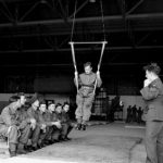 Inside a hangar, a British paratrooper learns to land correctly using a special harness, August 1942 (Imperial War Museum: H 22867)