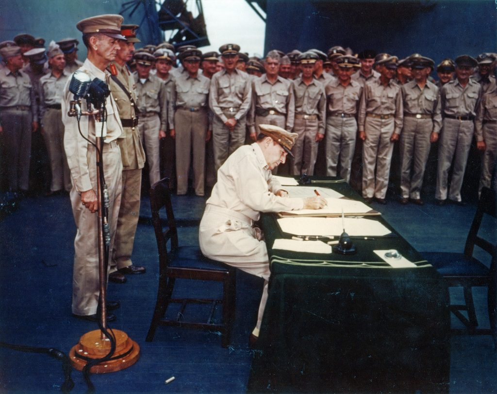 Gen. Douglas MacArthur signing the Japanese surrender documents aboard USS Missouri, 2 Sept 1945 (US National Archives: USA C-4627)