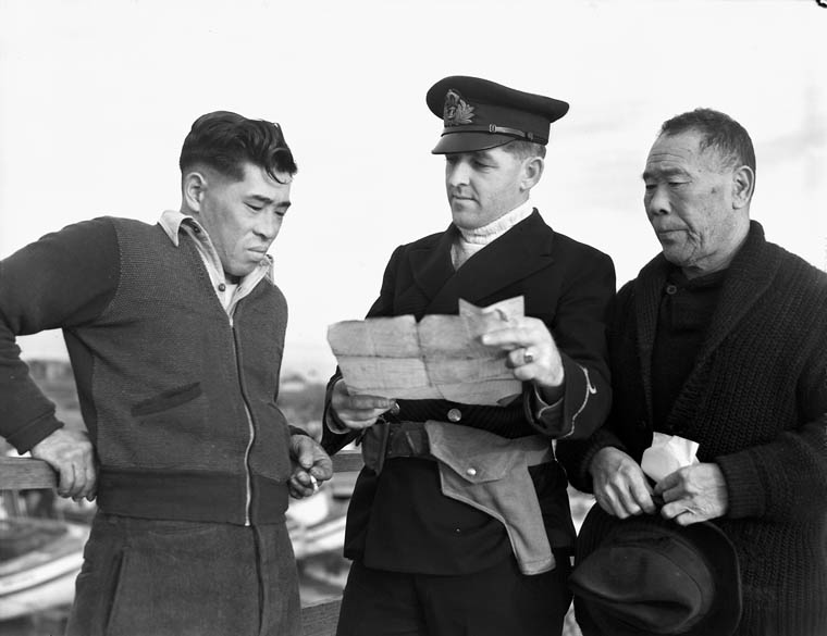 Royal Canadian Navy officer questioning Japanese-Canadian fishermen while confiscating their boat, 9 Dec 1941 (Library & Archives Canada)