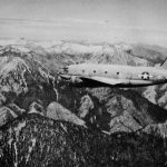 """US C-46 Commando cargo plane flying over the """"Hump"""" during World War II (US Army Air Forces photo)"""