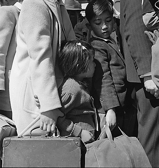 Japanese-American children waiting for bus to take them to an Assembly Center, Byron, CA, 2 May 1942 (US National Archives)