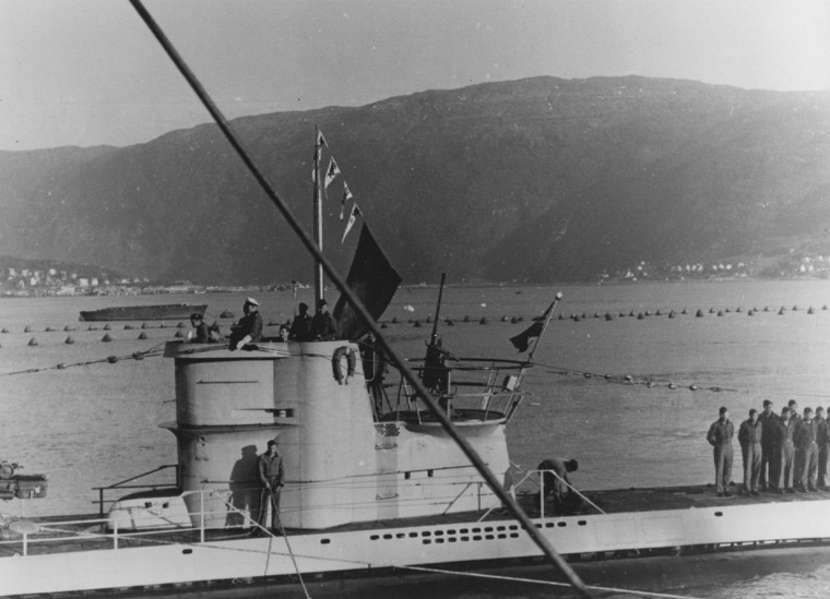 German U-boat U-255, painted white in Arctic camouflage, returning to port after attack on Convoy PQ-17, flying four victory pennants and the flag of the merchant ship Paulus Potter (US Naval History & Heritage Command: NH71317)