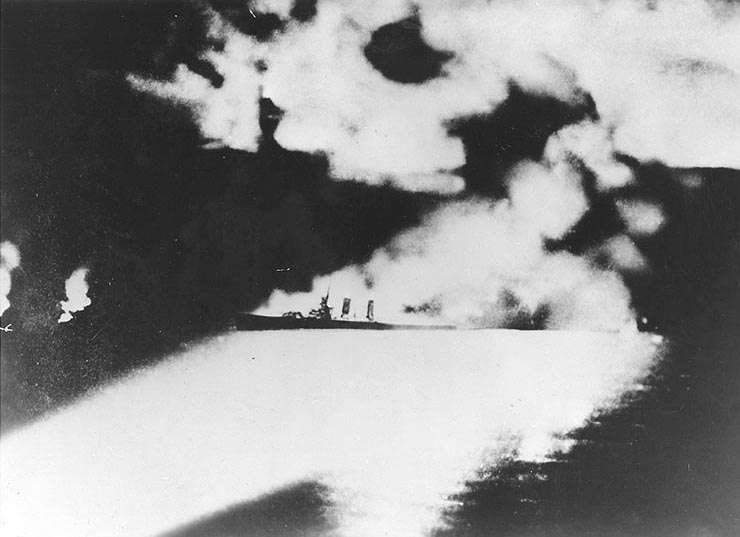 Heavy cruiser USS Quincy illuminated by Japanese searchlights during Battle of Savo Island, 9 Aug 1942 (public domain via WW2 Database)