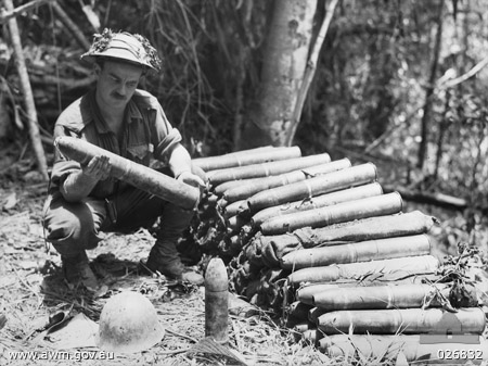 Australian soldier examines Japanese artillery shells abandoned at Ioribaiwa, New Guinea, Sept. 1942 (Australian War Memorial)