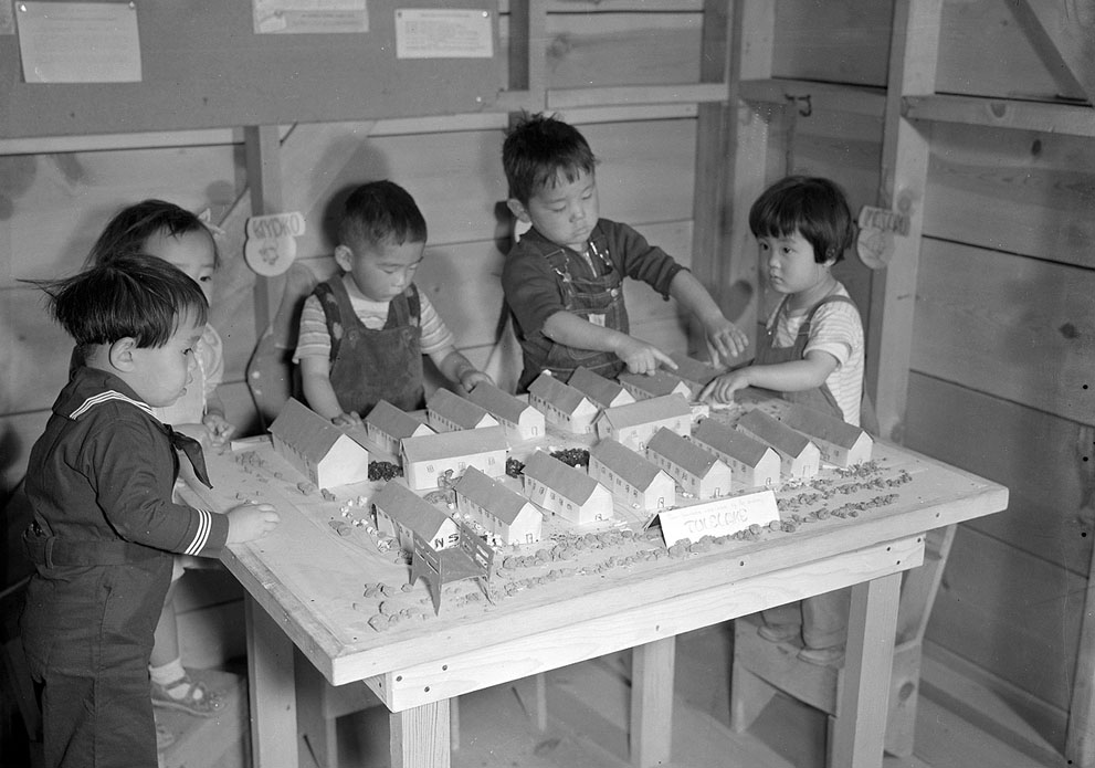 Japanese-American children playing with scale model of their home at Tule Lake Relocation Center, Newell, CA, 11 Sep 1942 (US National Archives)