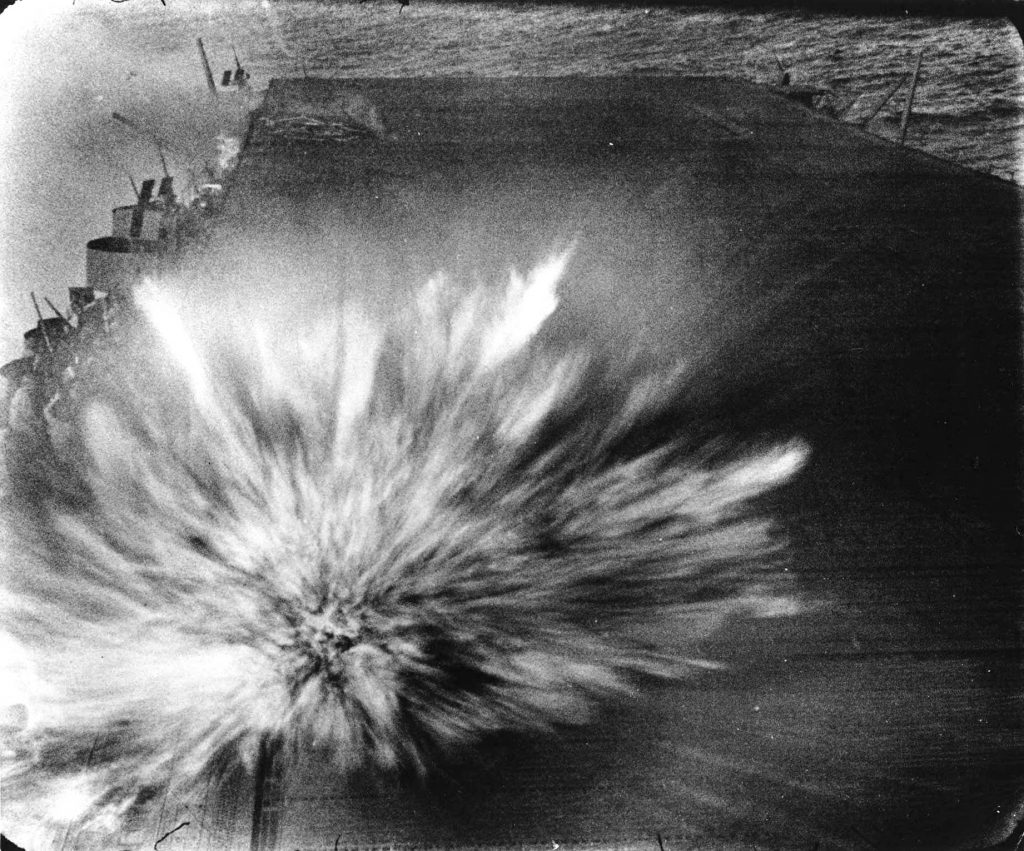 Bomb exploding on the flight deck of carrier USS Enterprise during Battle of the Eastern Solomons, 24 Aug 1942 (US National Archives)