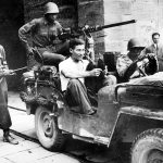 Soldiers of US 92nd Infantry Division with German prisoner captured in civilian clothes, Lucca, Italy, September 1944 (US National Archives)