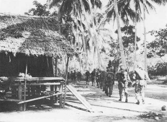 Troops of the US 128th Infantry Regiment passing through Simemi Village on way to Buna-Gona area, November 1942 (US Army Center of Military History)