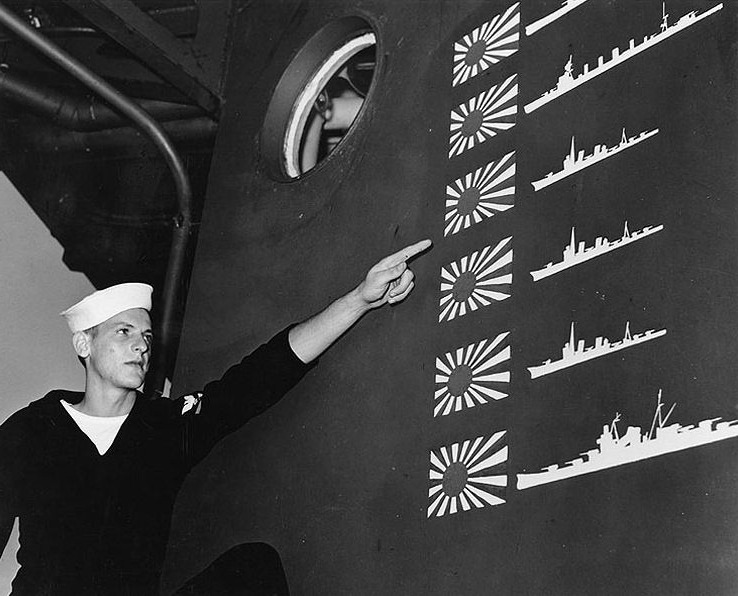 US sailor W.R. Martin points to scoreboard of light cruiser USS Boise from the Battle of Cape Esperance, 11-12 October 1942; the six Japanese ships claimed overstates actual enemy losses, not uncommon in night battles, Philadelphia Naval Shipyard, PA, November 1942 (US Naval History and Heritage Command).