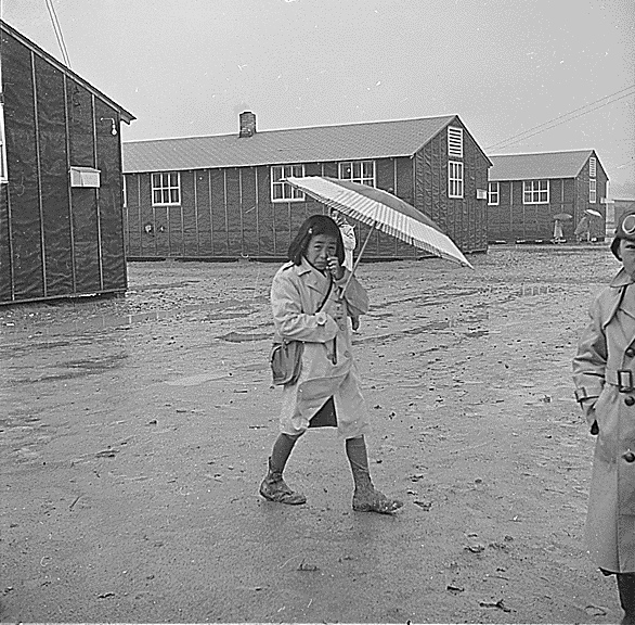 Japanese-American girl walking in rain, Jerome Relocation Center, AR, 12 Mar 1943 (US National Archives)