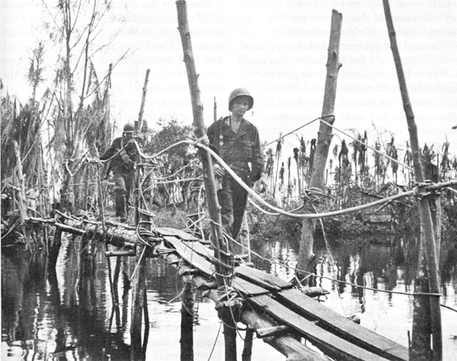 US troops crossing Japanese-built footbridge to Buna Mission over Entrance Creek, Papua New Guinea, December 1942.