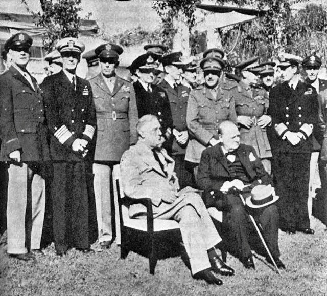 Allied leaders at the Casablanca Conference, January 1943. Seated: President Roosevelt and Prime Minister Churchill; standing, left to right: General Arnold, Admiral King, General Marshall, Admiral Pound, Air Chief Marshal Portal, General Brooke, Field Marshal Dill, and Admiral Mountbatten (public domain via Wikipedia)