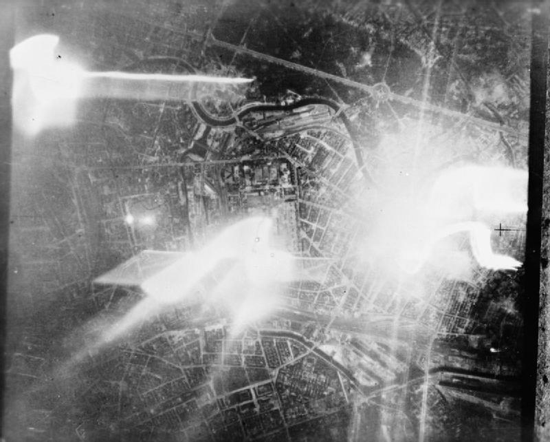 Berlin during a night raid by RAF Mosquitos; the track of a falling target indicator can be seen on the right, c. 1942-45 (Imperial War Museum)