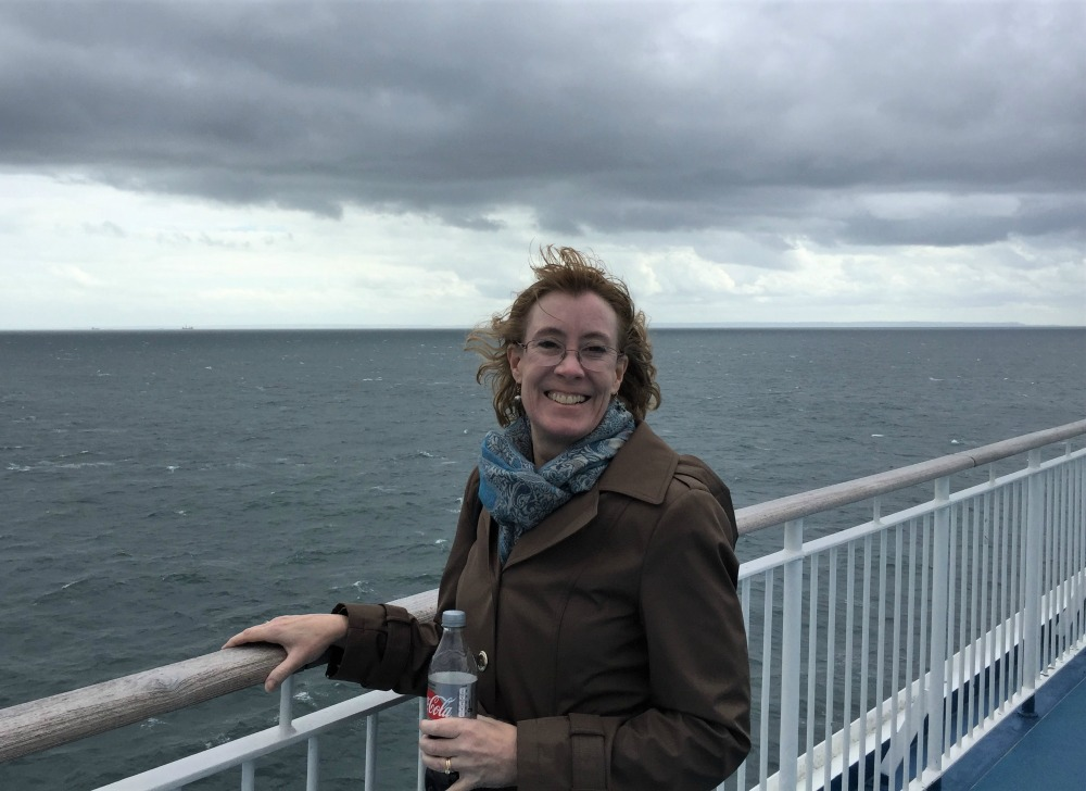 Sarah Sundin on ferry Mont St. Michel, with the shores of Normandy appearing on the horizon, September 2017