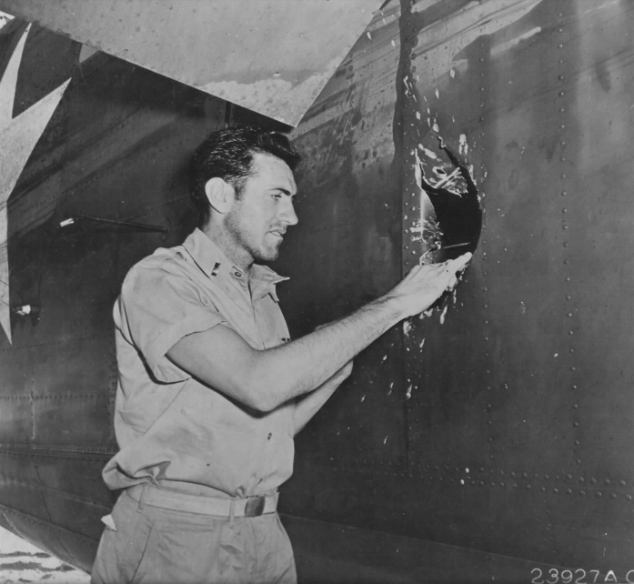 Lt. Louis Zamperini, bombardier, inspecting a hole in his B-24D Liberator, Superman, damaged over Nauru, 20 Apr 1943; photo taken at Funafuti in Gilbert Islands (US National Archives)