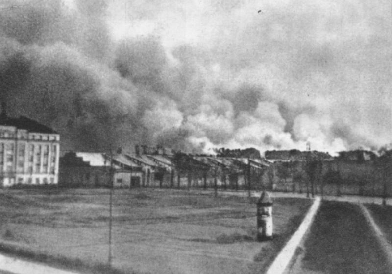 Burning buildings in the Warsaw Ghetto, late Apr 1943 (public domain via WW2 Database)