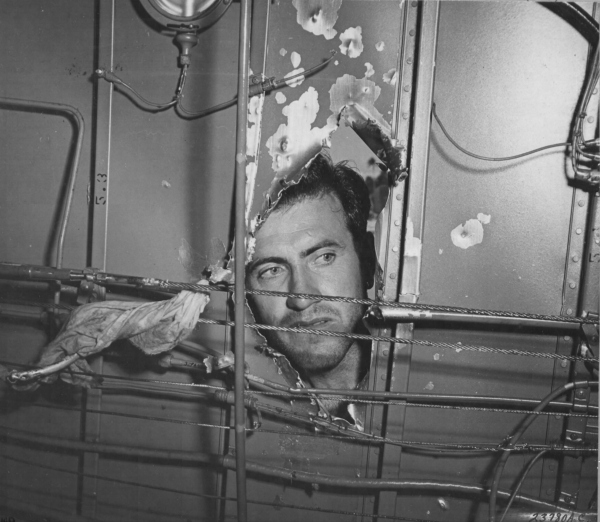 Lt. Louis Zamperini, bombardier, inspecting a hole in his B-24D Liberator, Superman, damaged over Nauru, 20 Apr 1943; photo taken at Funafuti in Gilbert Islands (US National Archives)