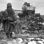 Russian mother and children looking at a destroyed home, Russia, 1 Sep 1943 (Russian International News Agency 982)