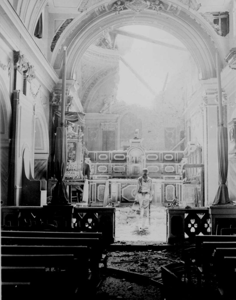 Pvt. Paul Oglesby of US 30th Infantry Regiment in a damaged Catholic Church at Acerno, Italy, 23 September 1943 (US National Archives)