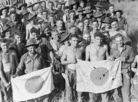 Soldiers from the 2/6th Independent Company display Japanese flags they captured during the battle of Kaiapit, 22 September 1943 (Australian War Memorial 057510)