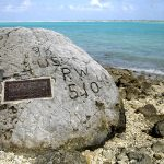 """Memorial for the 98 US civilian contract POWs who were executed by the Japanese on 7 Oct 1943; an unidentified prisoner escaped and chiseled """"98 US PW 5-10-43"""" on this rock before he was executed himself (US Air Force photo)"""