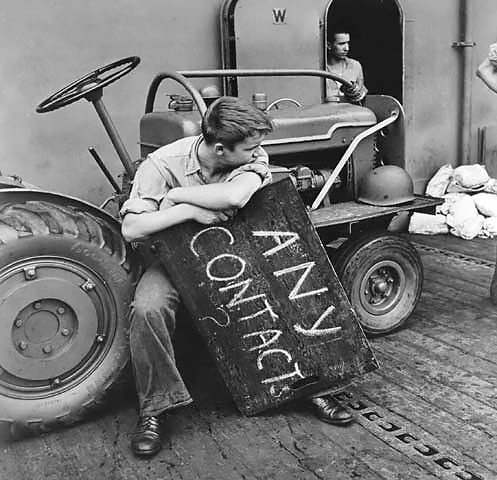 US aircraft carrier deck crewman resting between aircraft landings, off Tarawa, Gilbert Islands, Nov 1943 (US National Archives)
