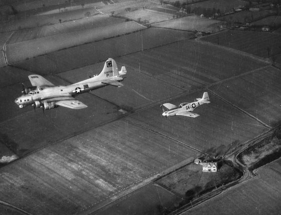 "B-17 Flying Fortress ""Maiden America"" of the 385th Bomb Group is escorted on a mission by two P-51 Mustangs, including P-51D ""Marymae"" of the 357th Fighter Group. (Imperial War Museum, Roger Freeman Collection)"