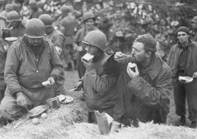 US troops eating Christmas dinner on a haystack, Italy, 25 December 1943 (US National Archives)