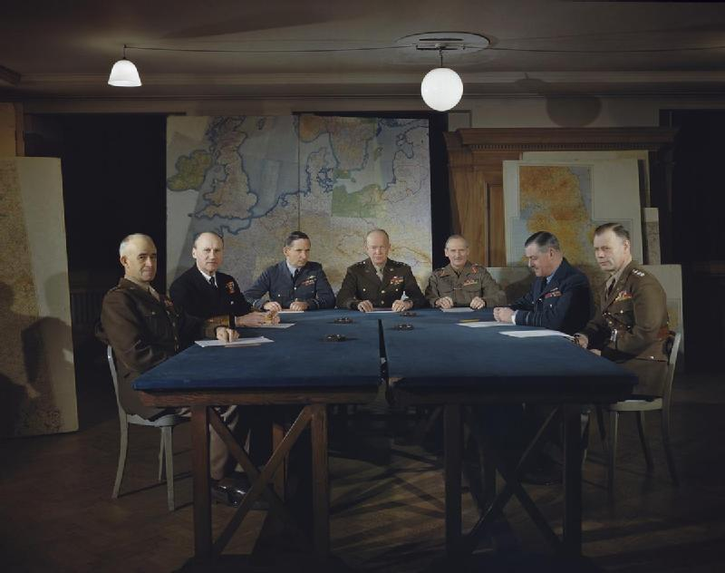 Gen. Omar Bradley, Adm. Bertram Ramsay, Air Chief Marshal Arthur Tedder, Gen. Dwight Eisenhower, Gen. Bernard Montgomery, Air Chief Marshal Trafford Leigh-Mallory, and Gen. Walter Bedell Smith at a SHAEF conference in London, England, 1 Feb 1944 (Imperial War Museum TR 1541)