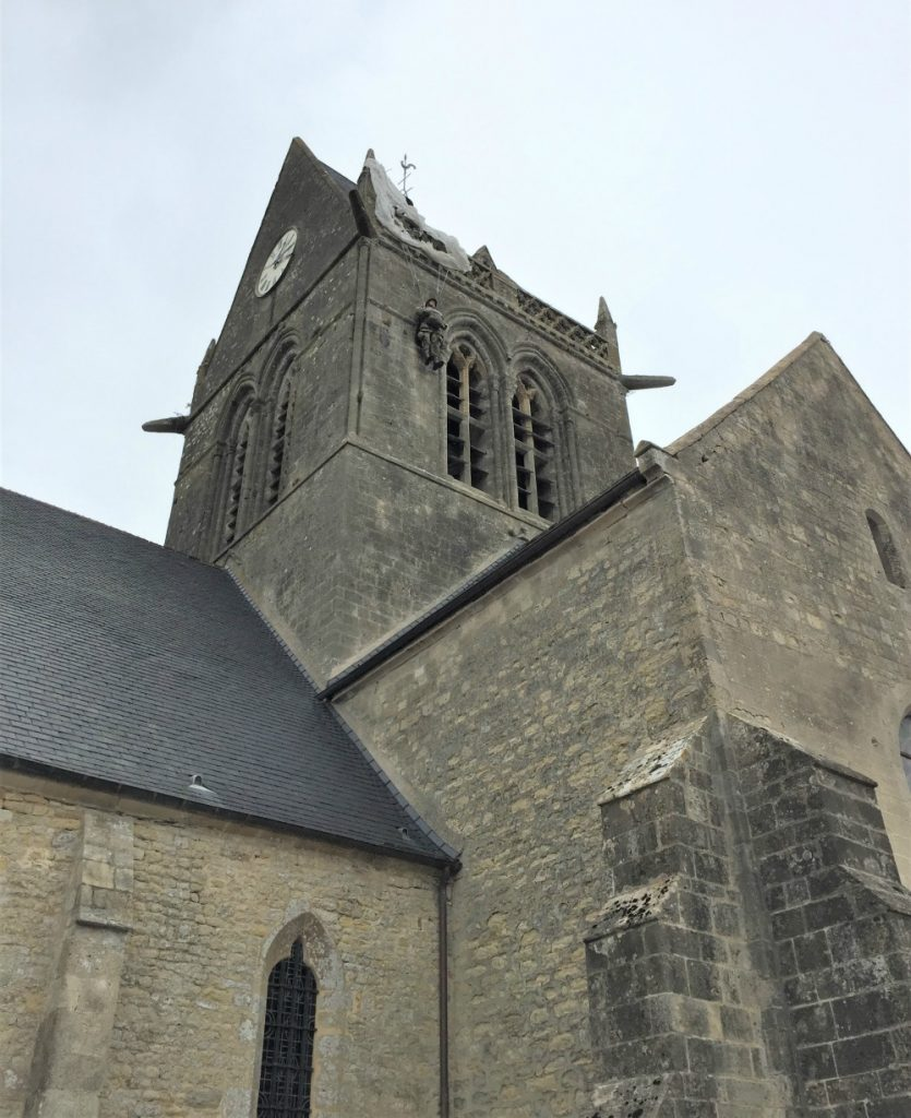 Close-up of church of Sainte-Mère-Église, France, showing memorial to paratrooper John Steele of the US 505th PIR, whose parachute caught on the steeple. He was taken prisoner by the Germans, but later escaped to fight again. (Photo: September 2017, Sarah Sundin)