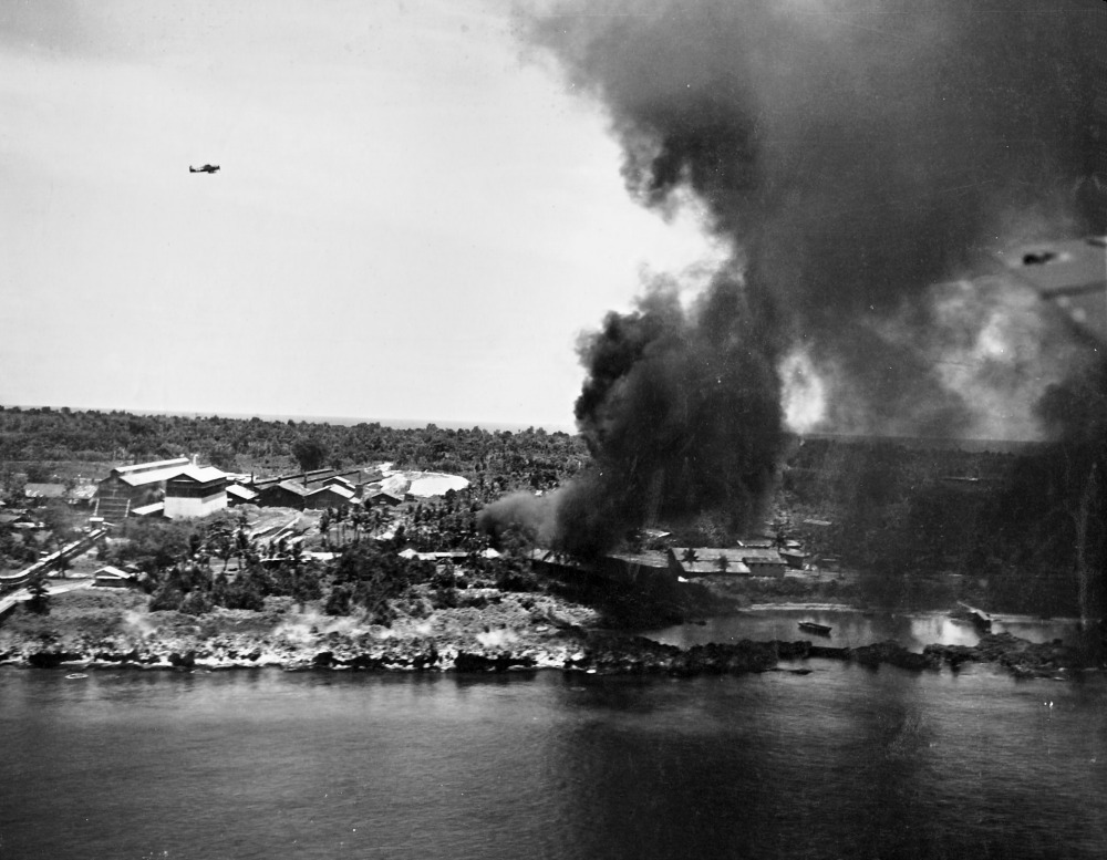 Peleliu Island under attack by aircraft of US Navy Task Force 58 (note F6F fighter in flight), 30 March 1944 (US National Museum of Naval Aviation)
