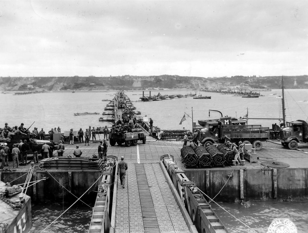 Military vehicles move ashore from Mulberry Artificial Harbor A, across a pontoon bridge, to Omaha Beach, Normandy, June 16 1944 (US National Archives)