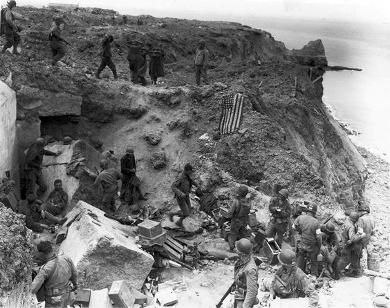 US 2nd Ranger Battalion at Pointe du Hoc after relief on D+2 (June 8, 1944), when American flag had been spread out to stop fire of friendly tanks coming from inland. Some German prisoners are being moved in after capture (US Army Signal Corps photo)