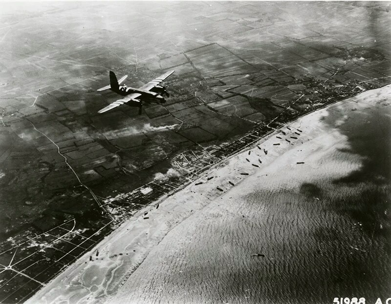US B-26 Marauder over Utah Beach, 6 June 1944. The medium bomber has been specially marked for D-day with black and white stripes on the fuselage and wings, which were to identify itself as a friendly aircraft to ground units. (USAF photo)