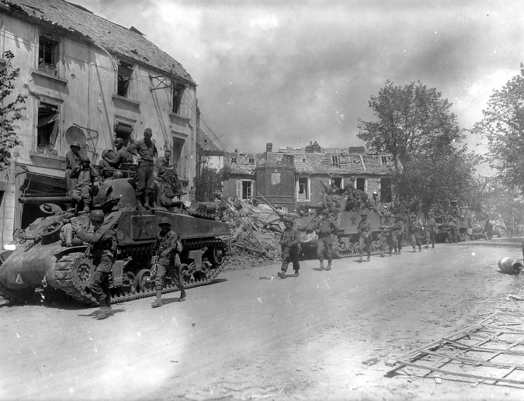 American armored and infantry forces pass through the battered town of Coutances, France, July 1944 (US National Archives)