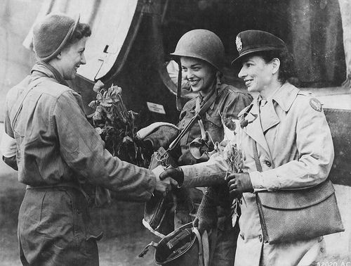 Flight nurses Lt. Suella Bernard and Lt. Marijean Brown, the first nurses to evacuate the wounded from Normandy to England, are greeted by their head nurse, Lt. Foster. (US Air Force photo)