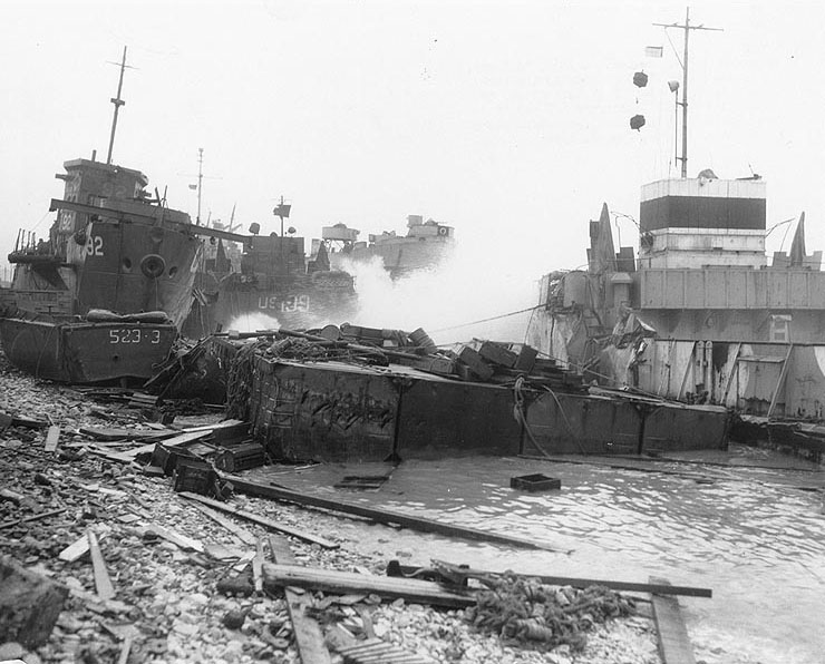 Broached landing craft during the Normandy storm, probably at Omaha Beach, 21 June 1944; USS LST-543 in background (US National Archives)