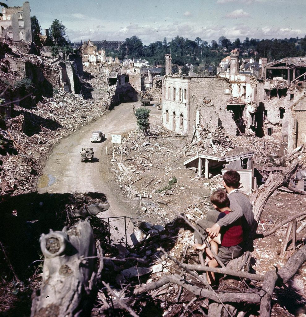 Two French boys watch as Allied vehicles pass through the ruins of Saint-Lô, France, July-August 1944 (US National Archives)