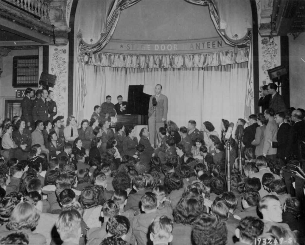 Bing Crosby singing at the opening of the Stage Door Canteen in London, 31 August 1944 (US National Archives)